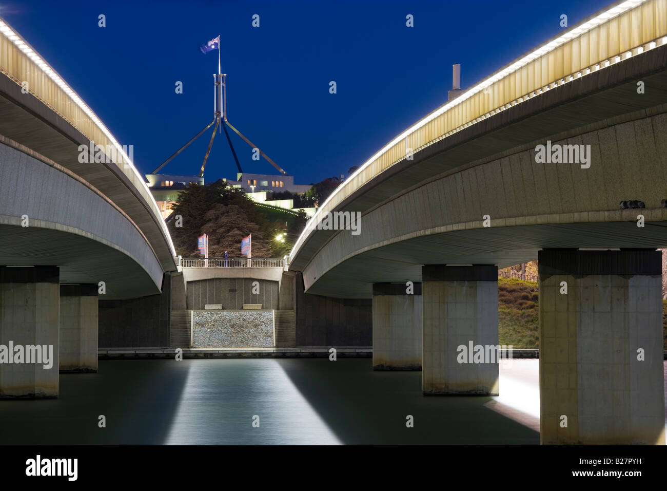 Australian Parliament House with Flagpole seen through Commonwealth Avenue Bridge over Lake Burley Griffin, Canberra. - Stock Image