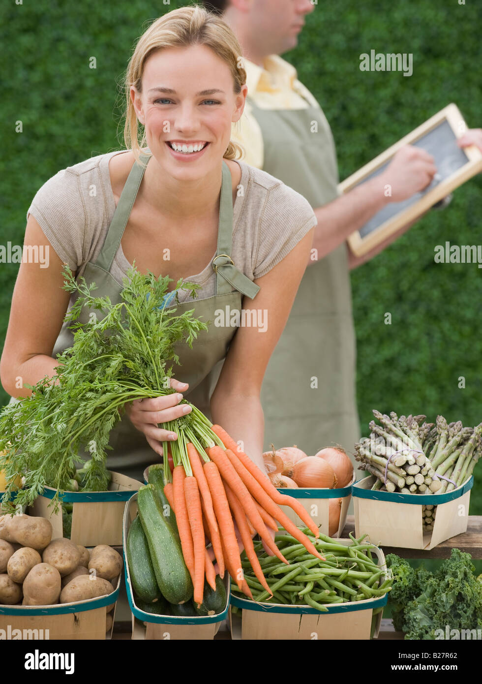 Woman next to baskets of vegetables - Stock Image