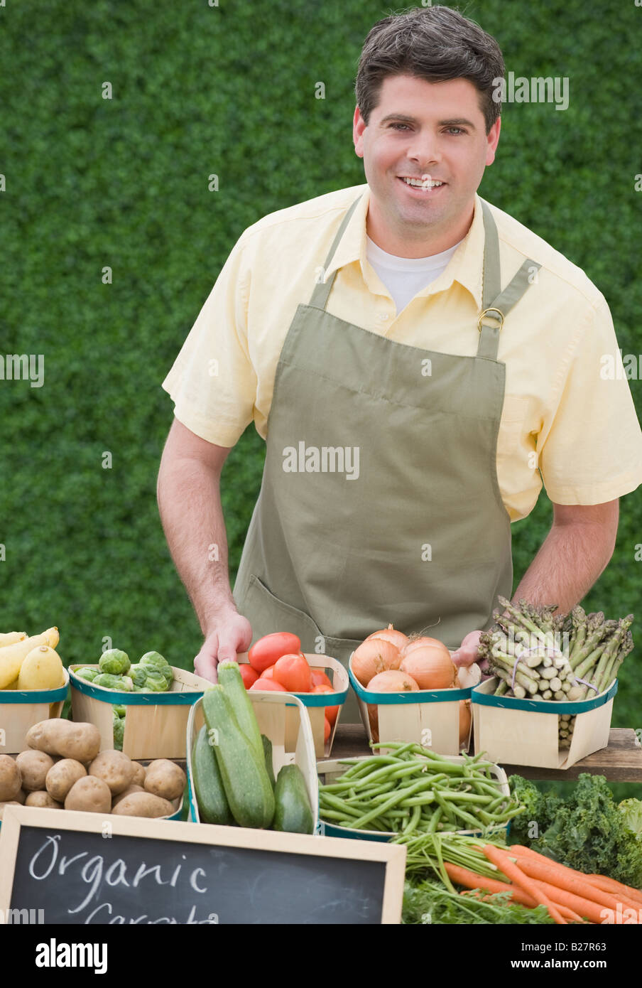 Man next to baskets of vegetables - Stock Image