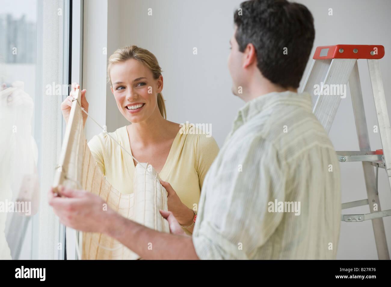 Couple hanging window blinds - Stock Image