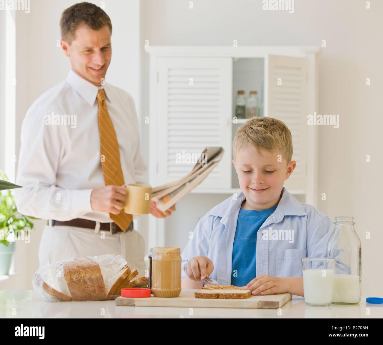 Father watching son make sandwich - Stock Image