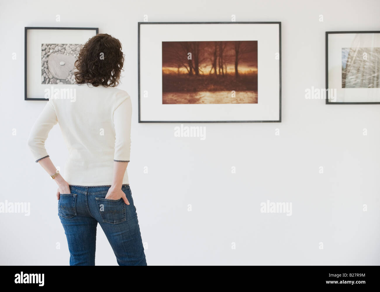 Woman looking at art in art gallery - Stock Image