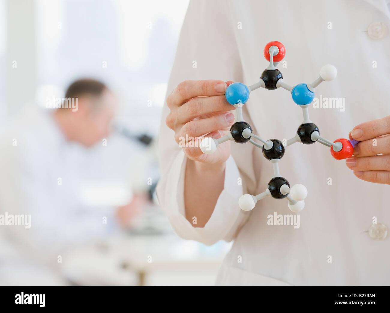Female scientist holding molecular model - Stock Image