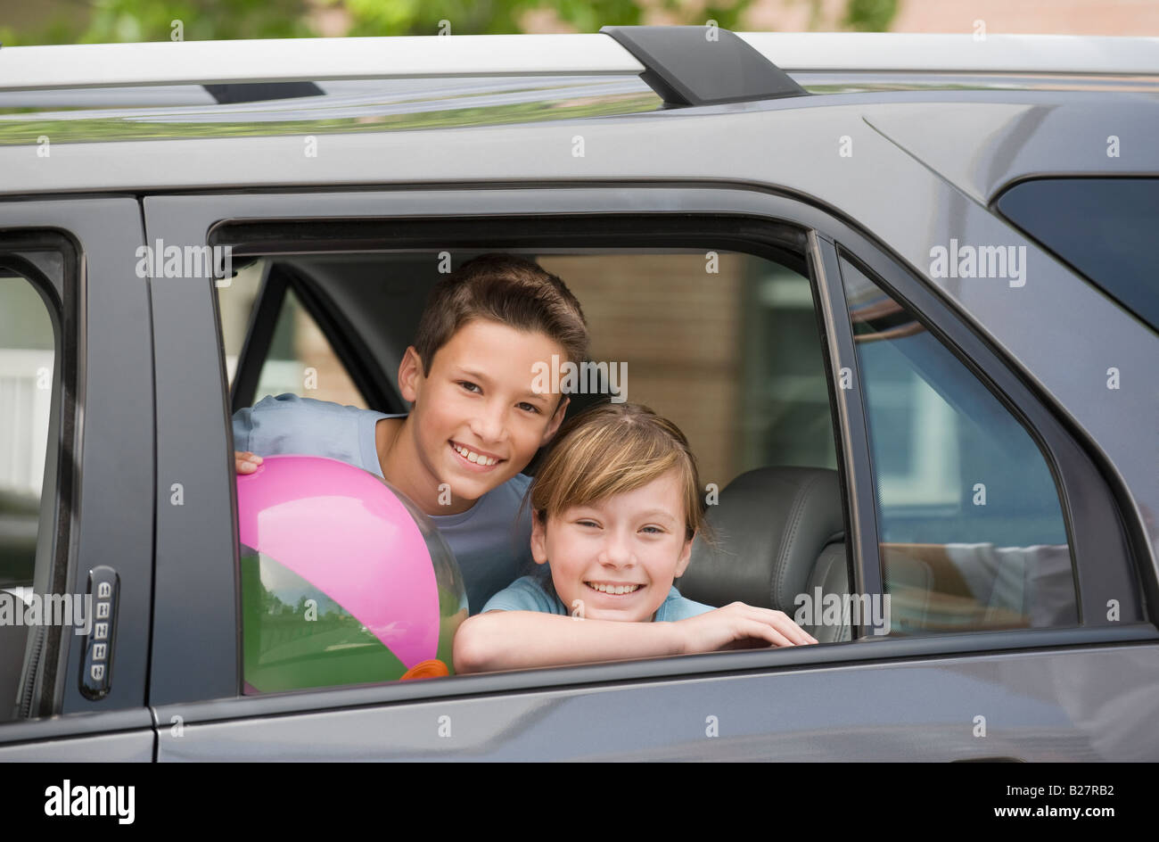 brother and sister looking out car window stock photo