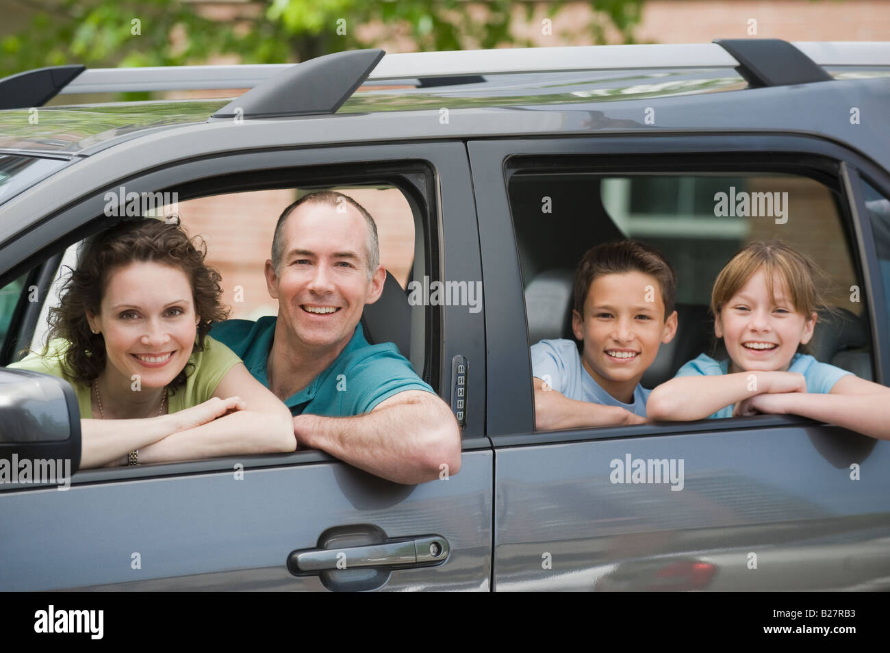 Family with two children looking out car windows - Stock Image