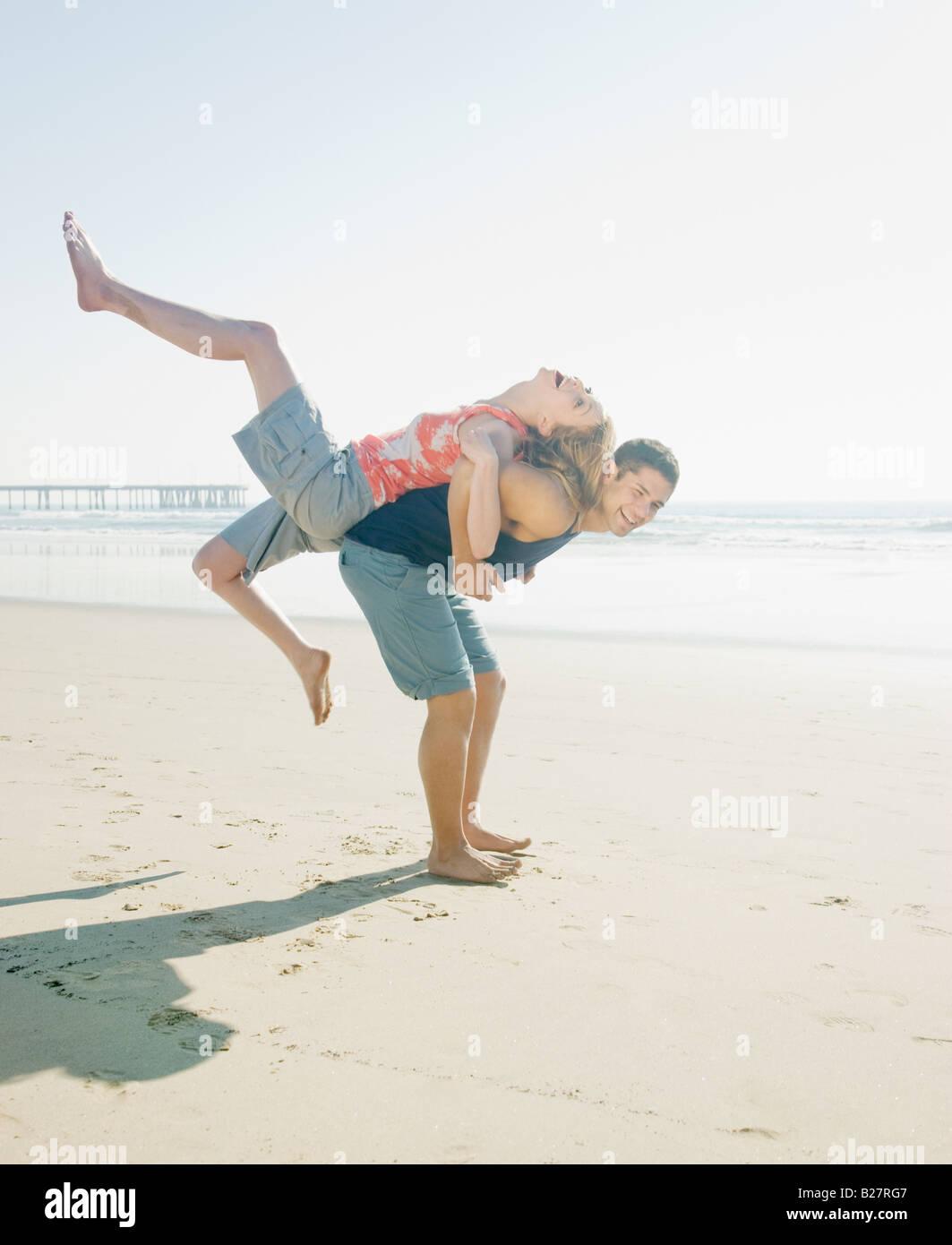 Couple playing around on beach - Stock Image