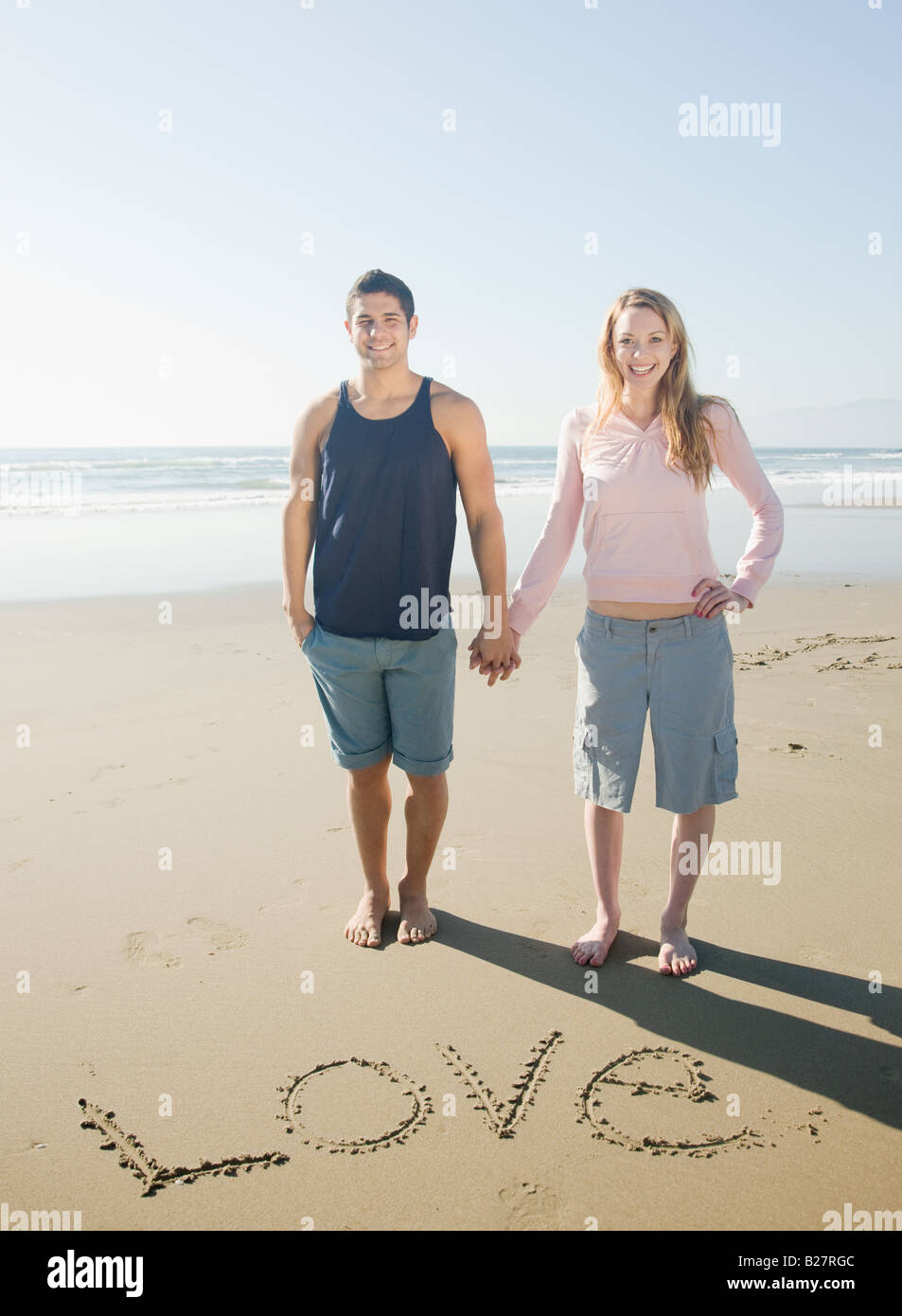 Couple next to Love written in sand Stock Photo