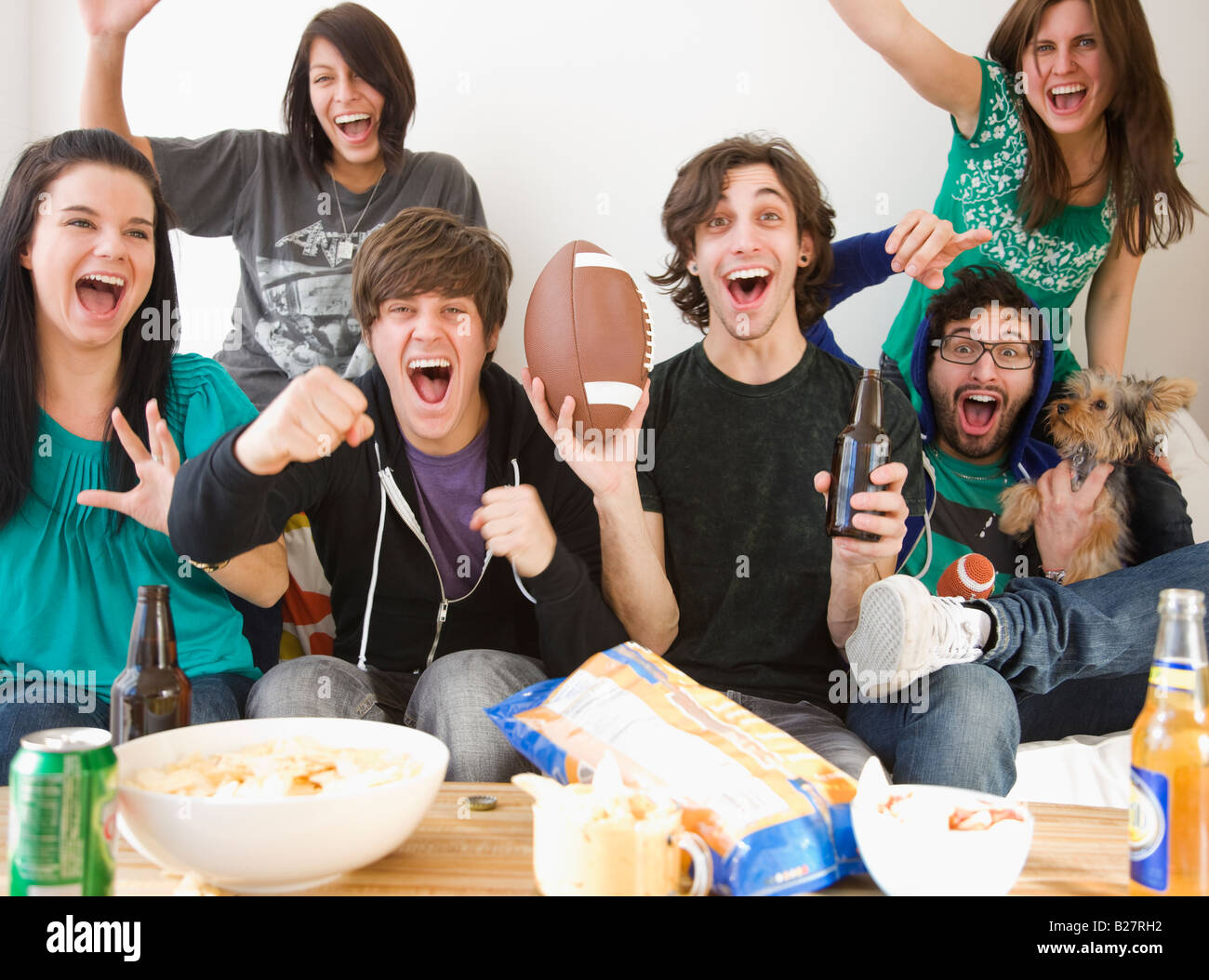 Group of friends cheering on sofa - Stock Image