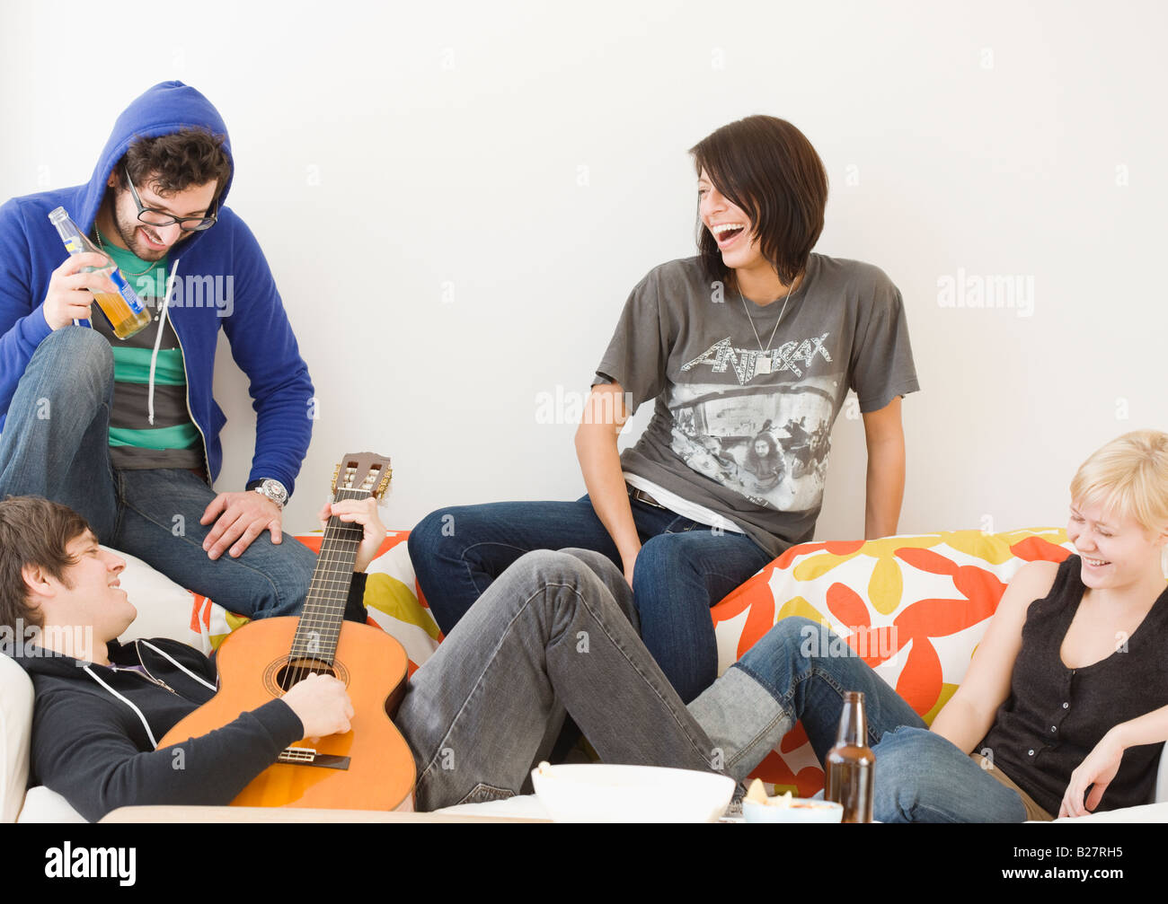 Group of friends relaxing on sofa - Stock Image