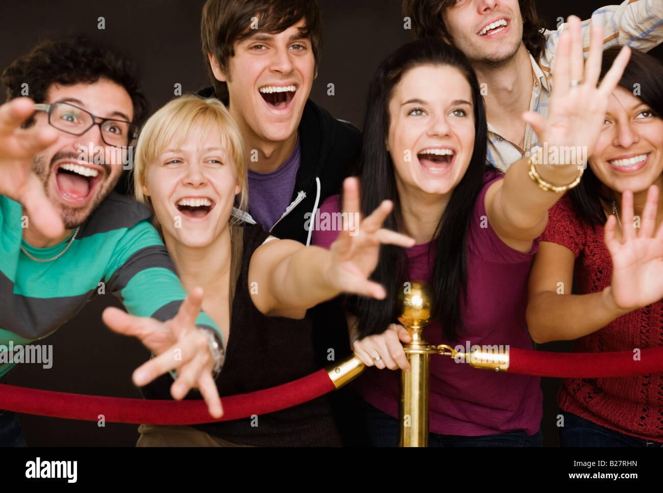 group of people reaching across velvet rope - Stock Image