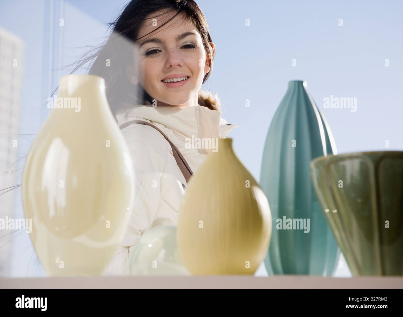 Woman looking at pottery in window - Stock Image
