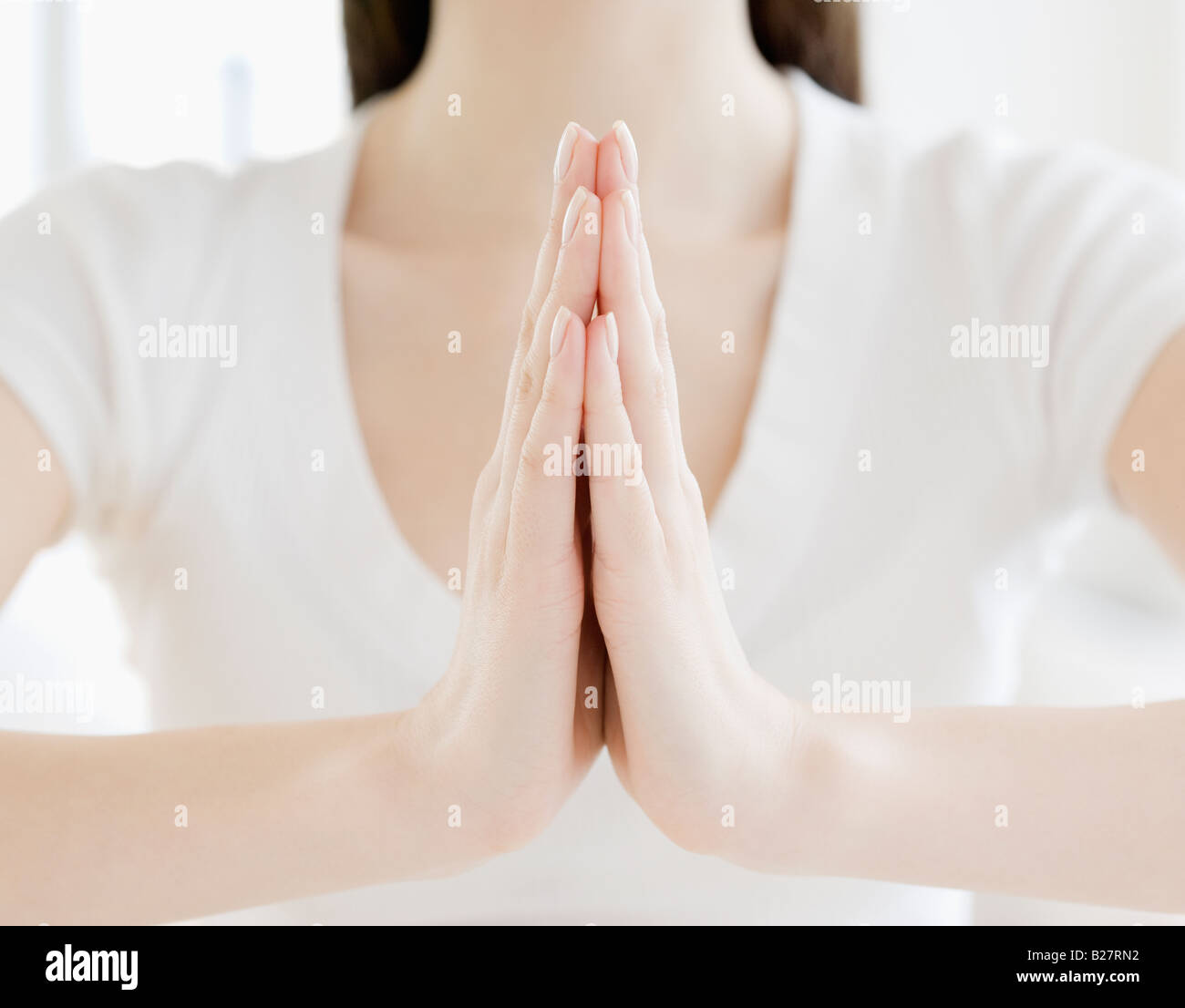 Close up of woman's hands with palms pressed together - Stock Image