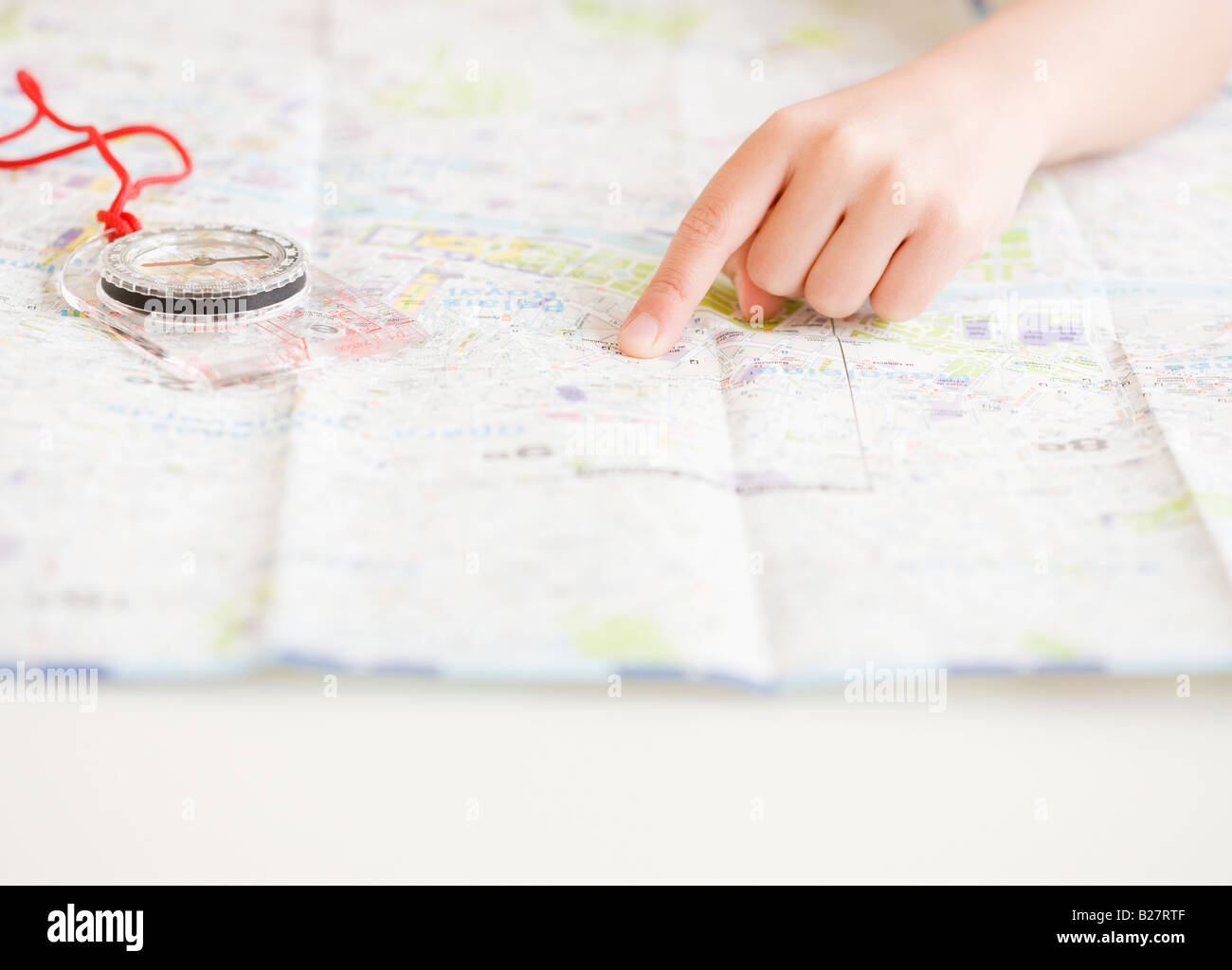 Child pointing at map next to compass - Stock Image