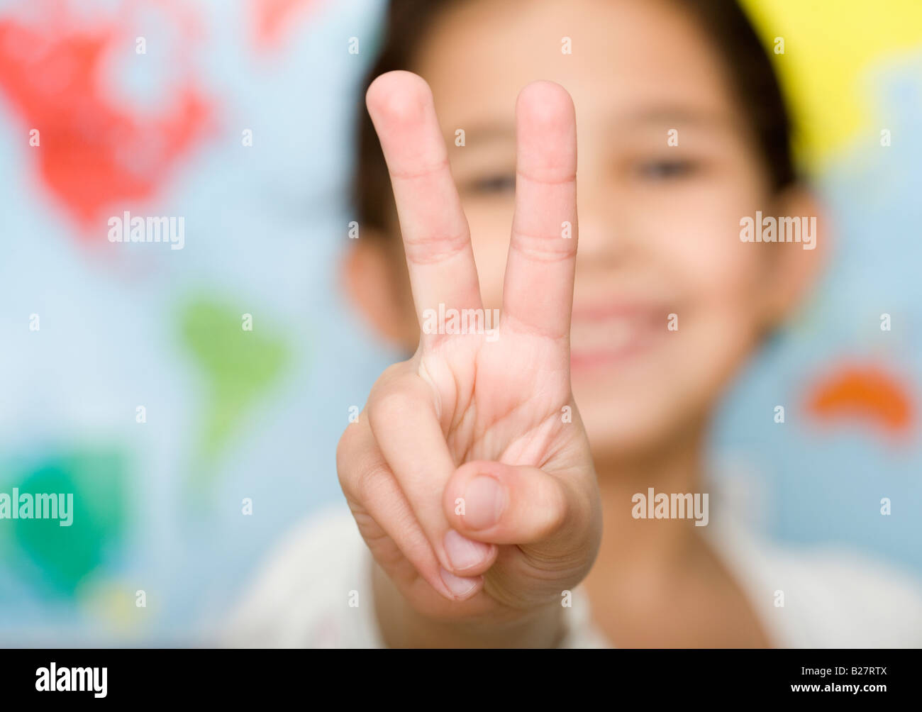 Child making peace sign hand gesture - Stock Image