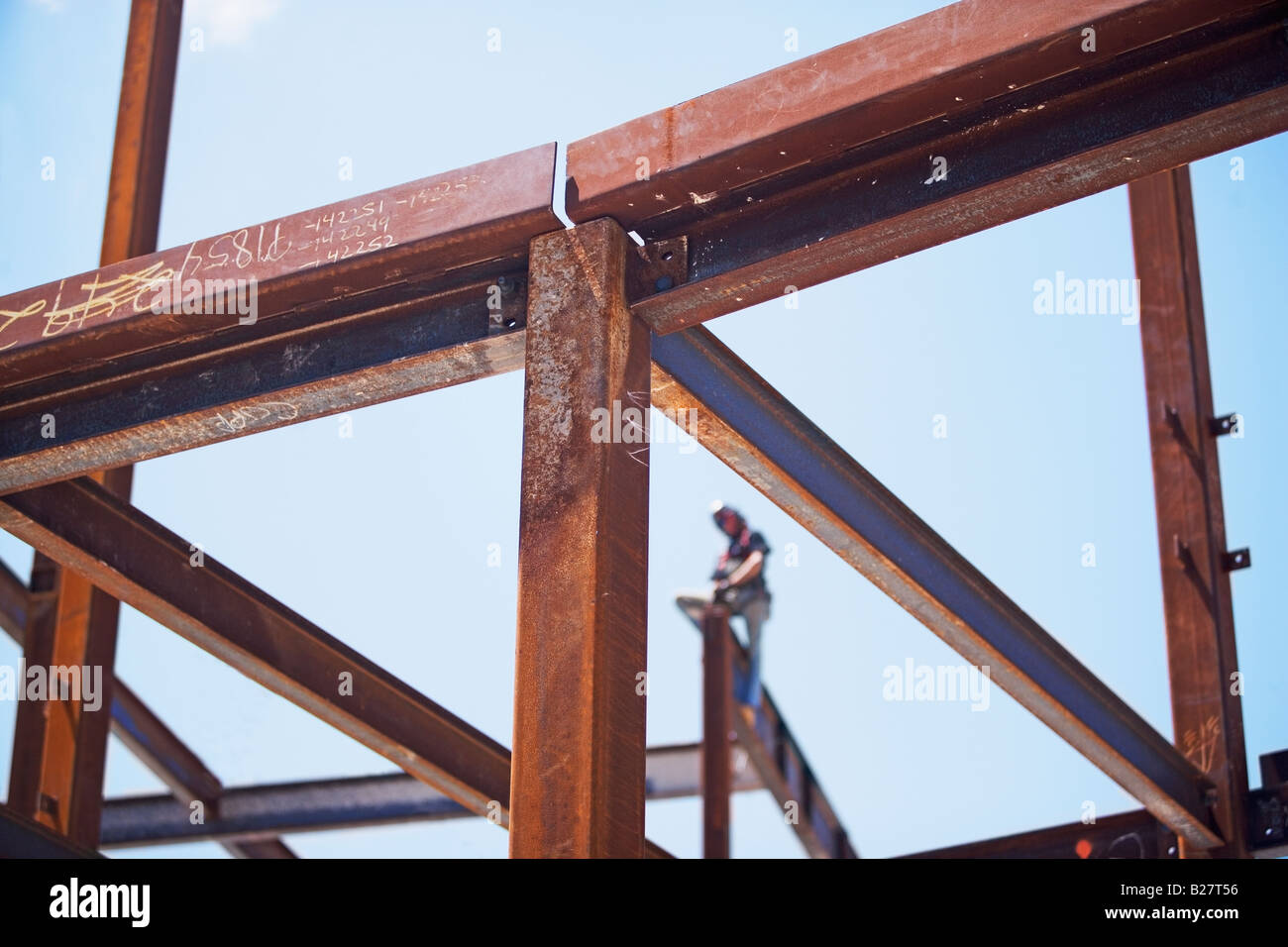 Construction worker on steel beam at construction site - Stock Image