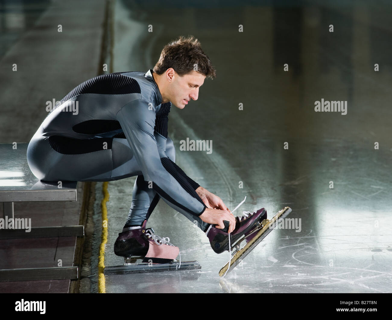 Male speed skater ties skate lace - Stock Image