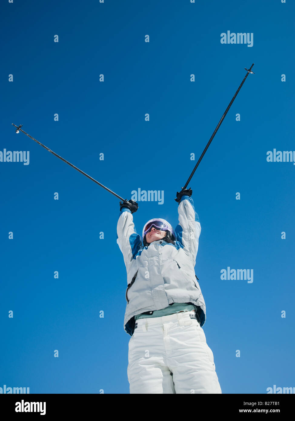 Woman holding ski poles over head - Stock Image
