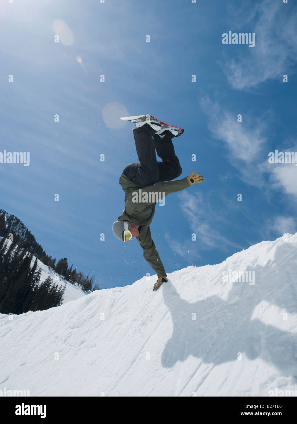 Man performing trick on snowboard - Stock Image