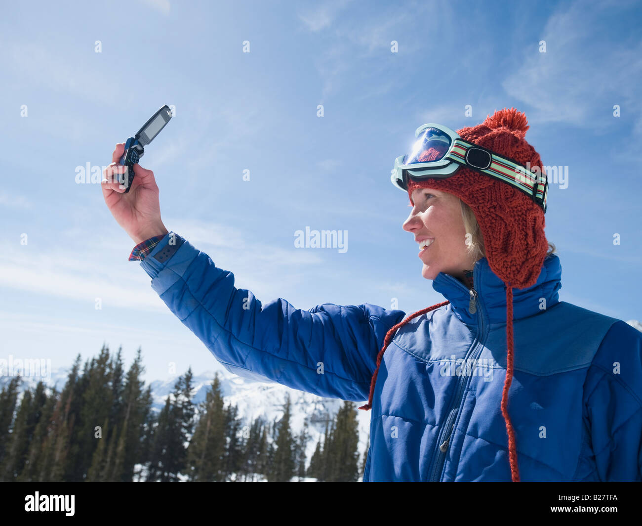 Woman in ski gear taking photograph - Stock Image