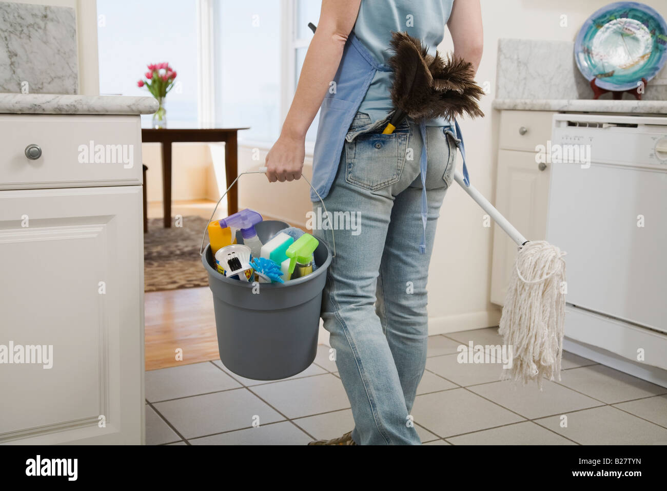 Woman holding mop and cleaning supplies - Stock Image