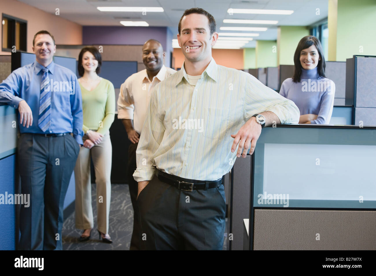 Businessman with multi-ethnic coworkers in background - Stock Image