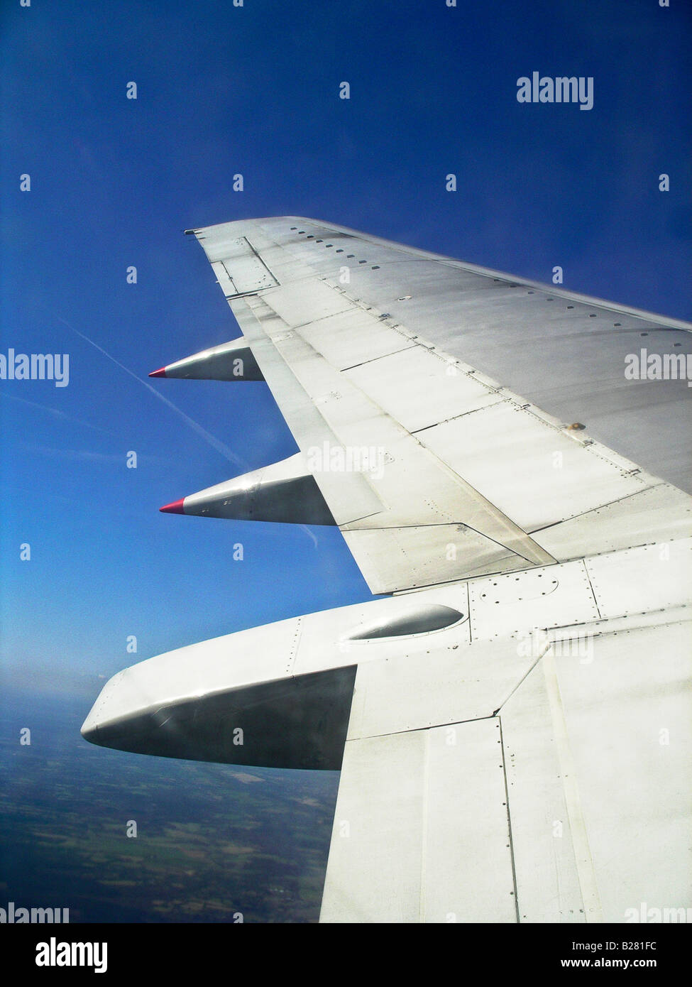 Aircraft port wing mainplane in flight at altitude Seen through passenger window - Stock Image