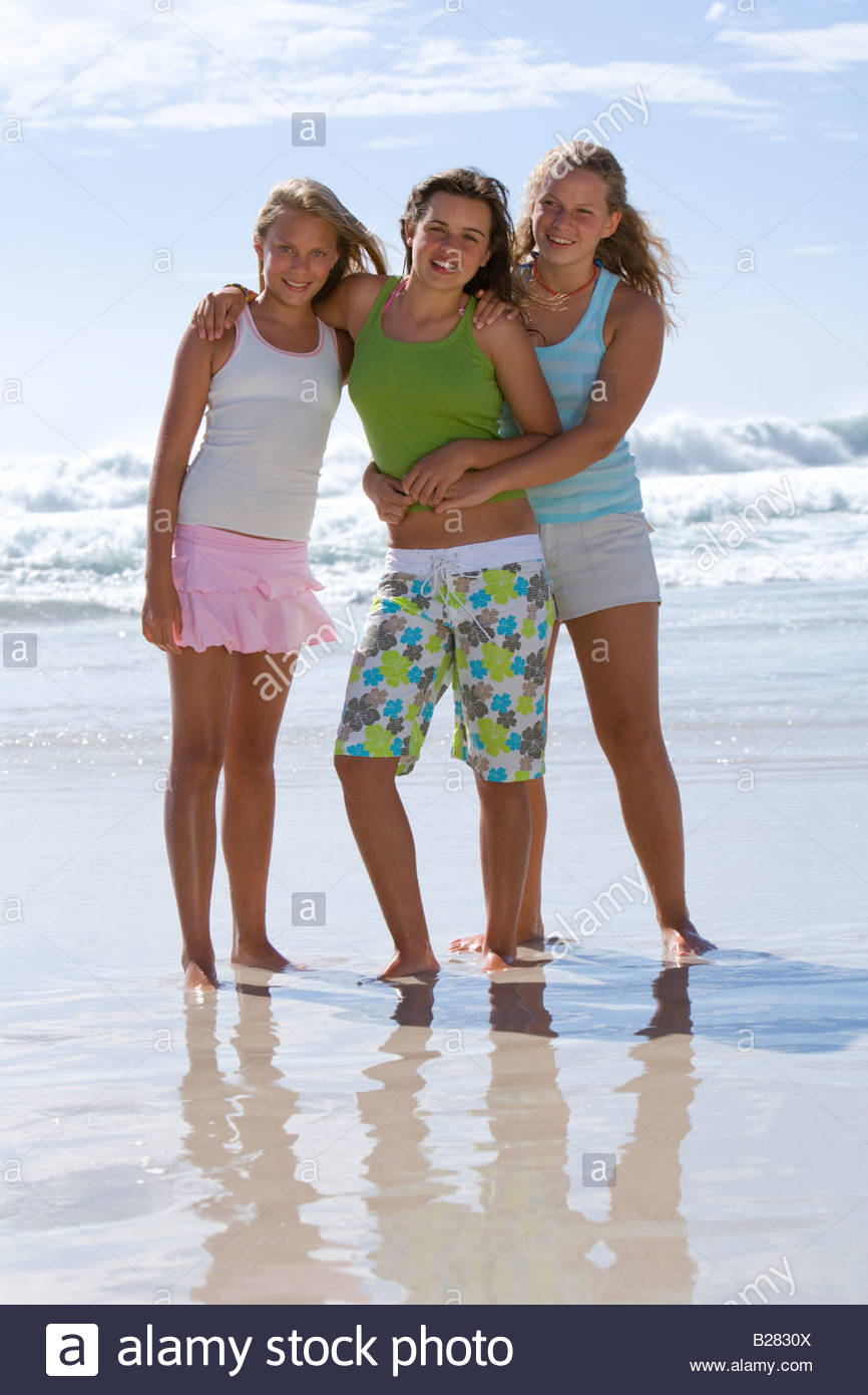 Three teenage girls (14-16) arm in arm on beach, smiling, portrait - Stock Image