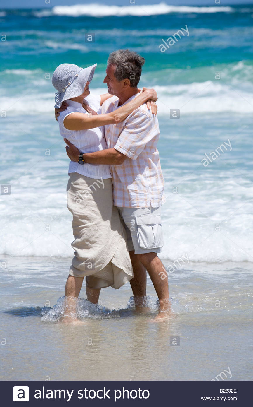 Mature couple embracing in shallows on beach Stock Photo