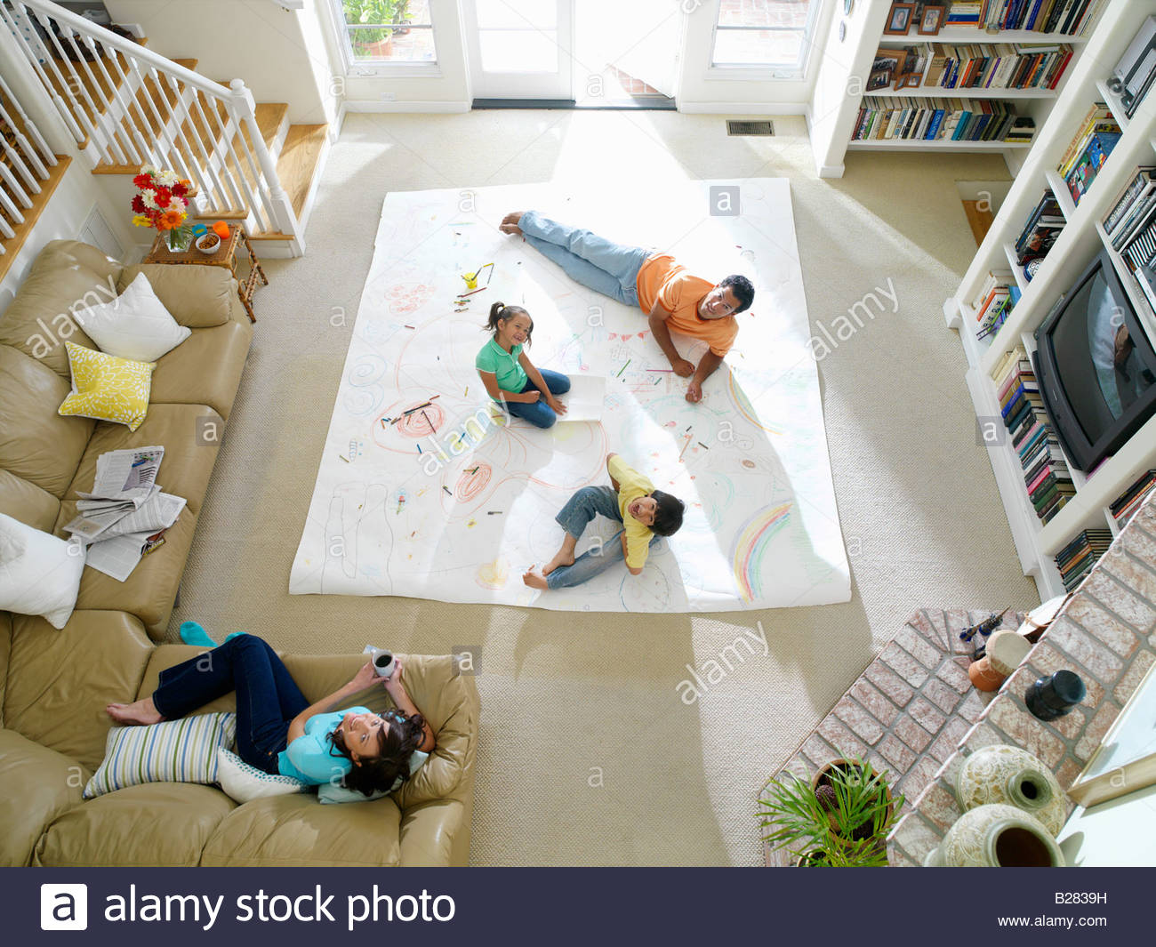 Family of four in living room, drawing on large piece of paper on floor, elevated view - Stock Image