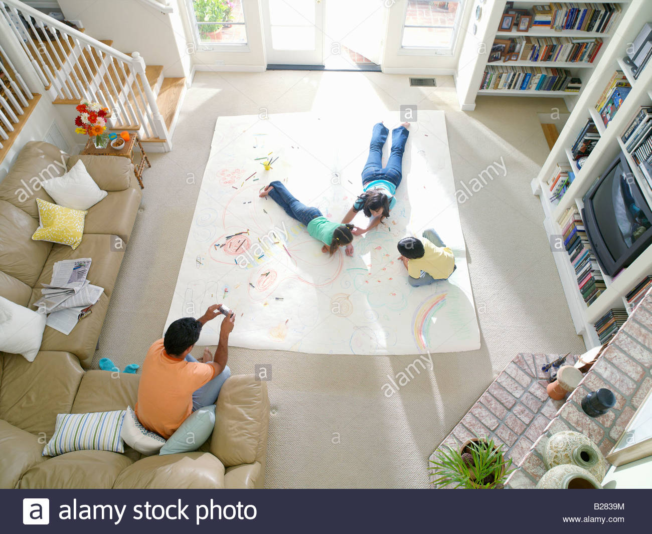 Family of four in living room, mother, son and daughter (6-10) drawing on large piece of paper on floor, elevated - Stock Image