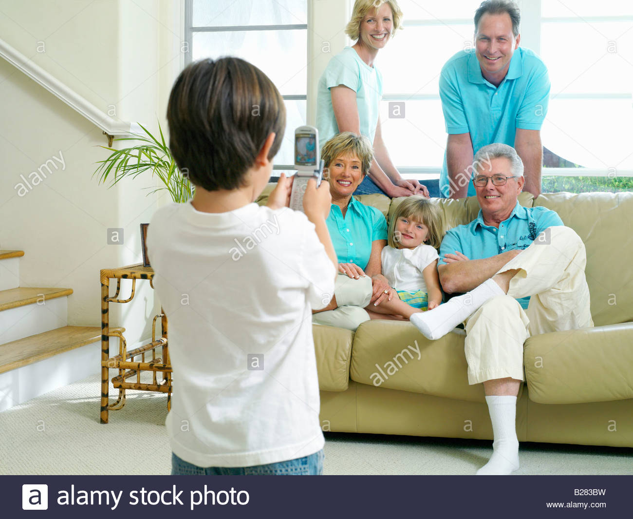 Boy (7-9) taking photograph with mobile phone of parents, grandparents and sister (6-8) on sofa, smiling - Stock Image