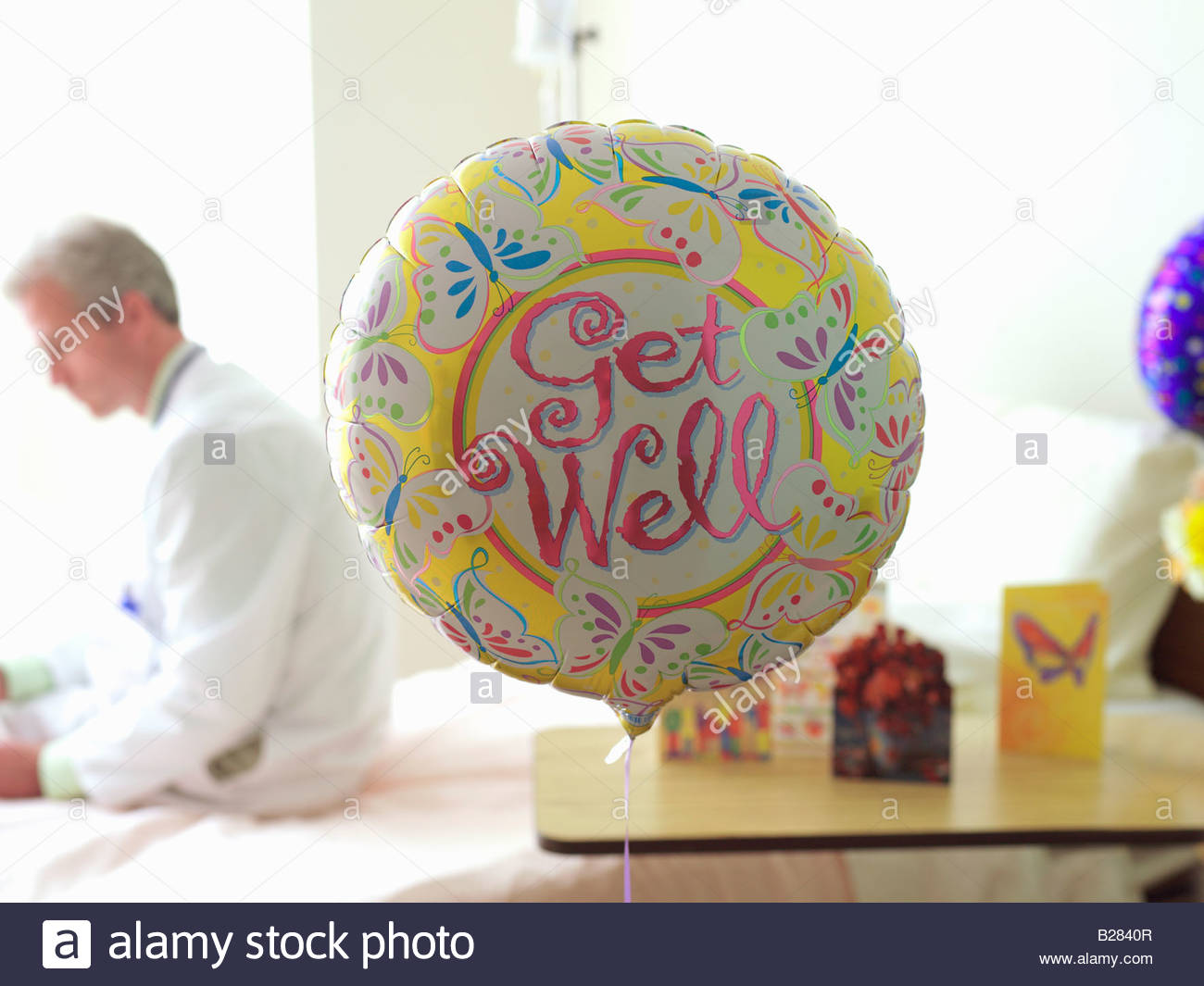 'Get Well' balloon in hospital, doctor in background - Stock Image