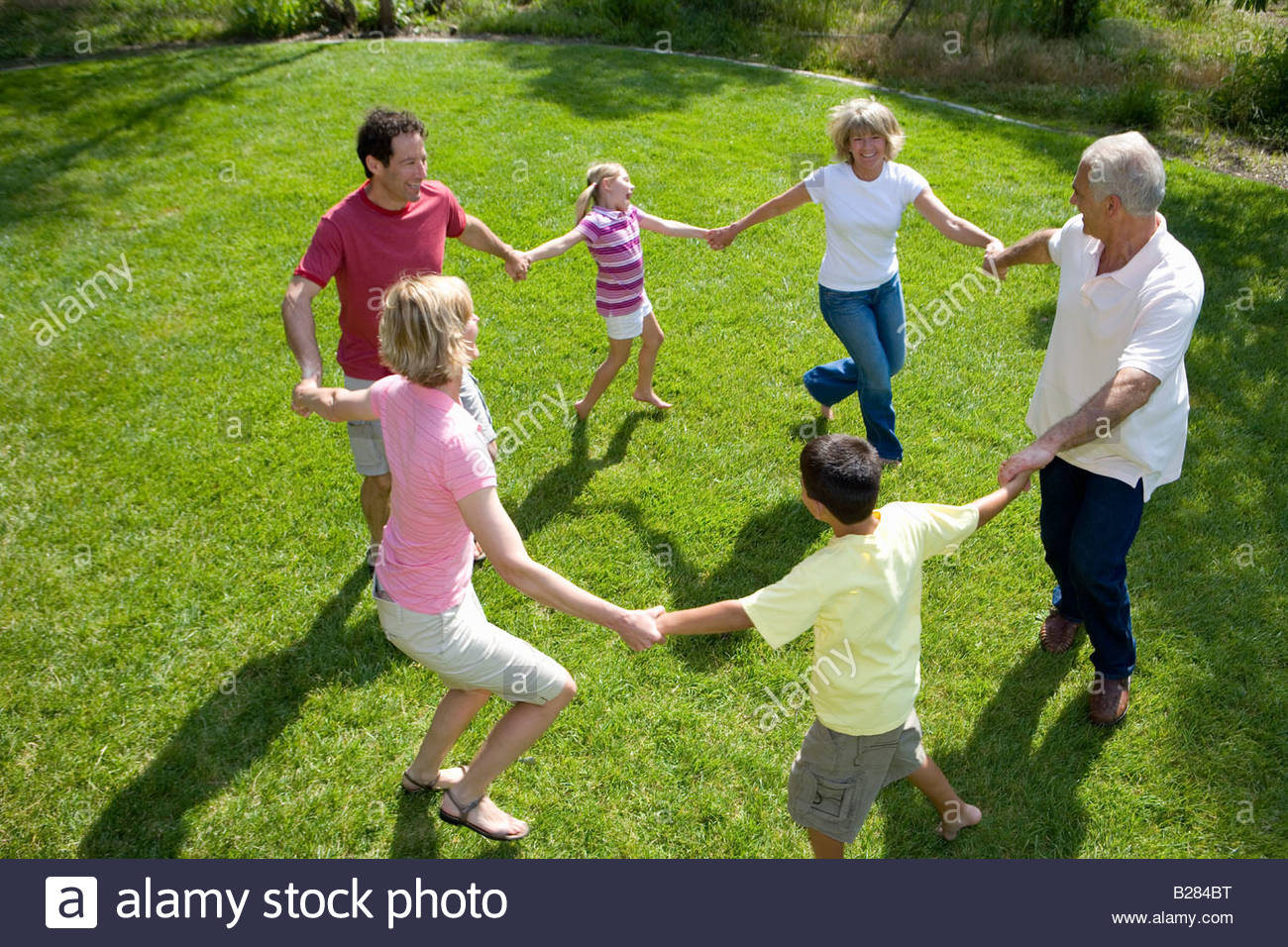Family of three generations holding hands in circle in garden, elevated view - Stock Image