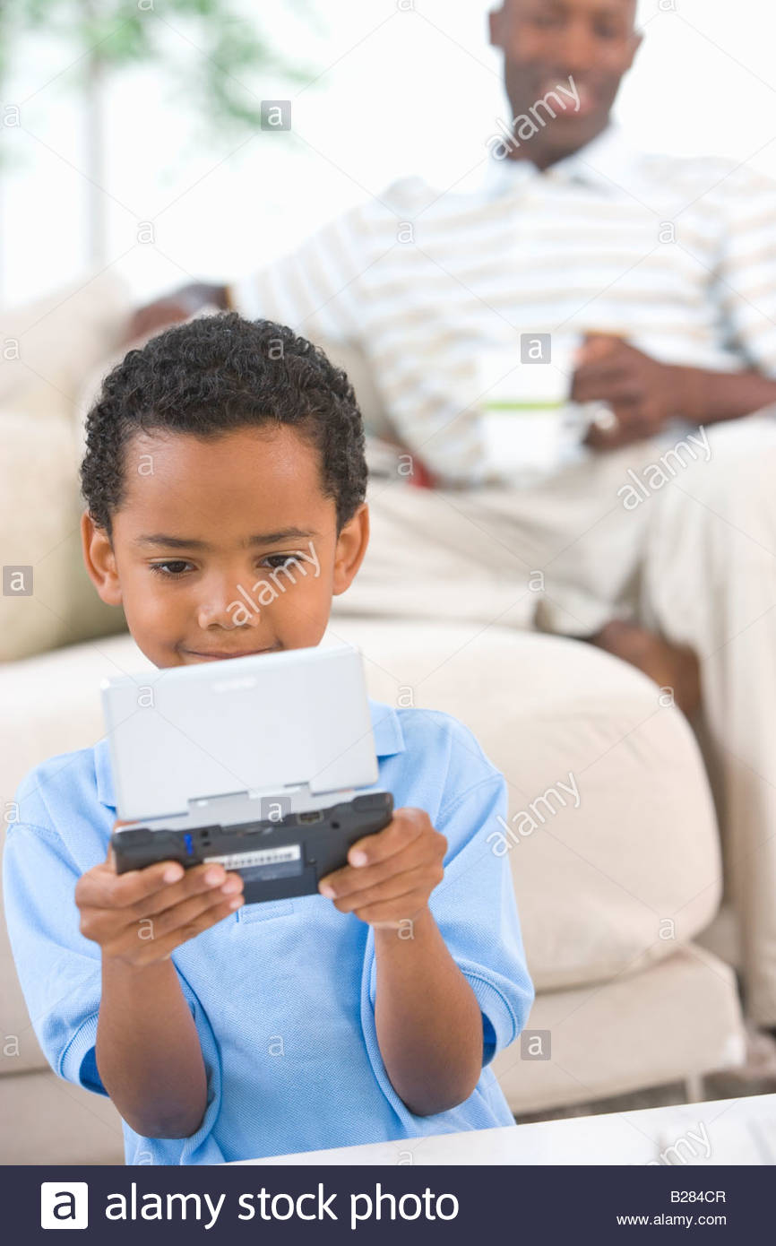 Boy (6-8) playing computer game, father in background - Stock Image