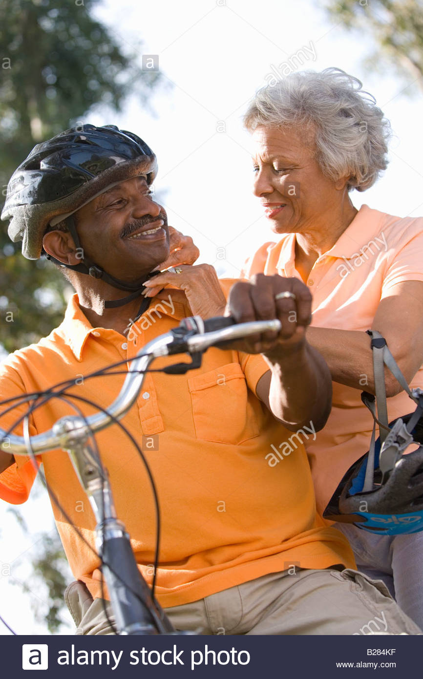 Senior woman adjusting man's bicycle helmet, low angle view - Stock Image