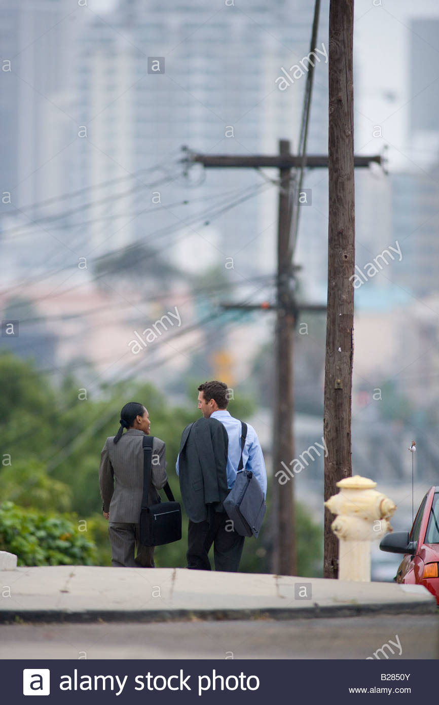 Businessman and woman walking outdoors, rear view - Stock Image