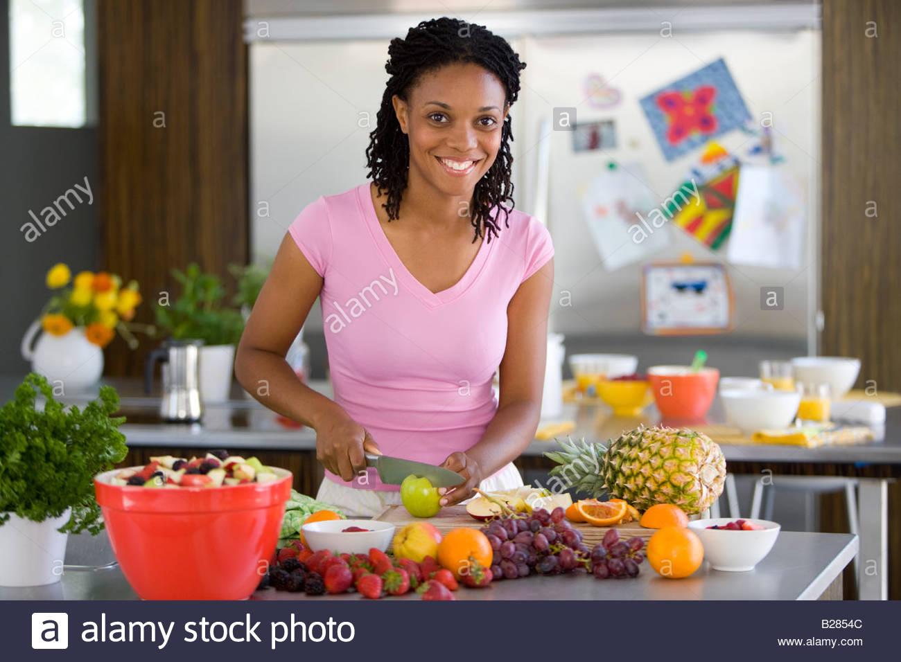 Woman making fruit salad, portrait - Stock Image
