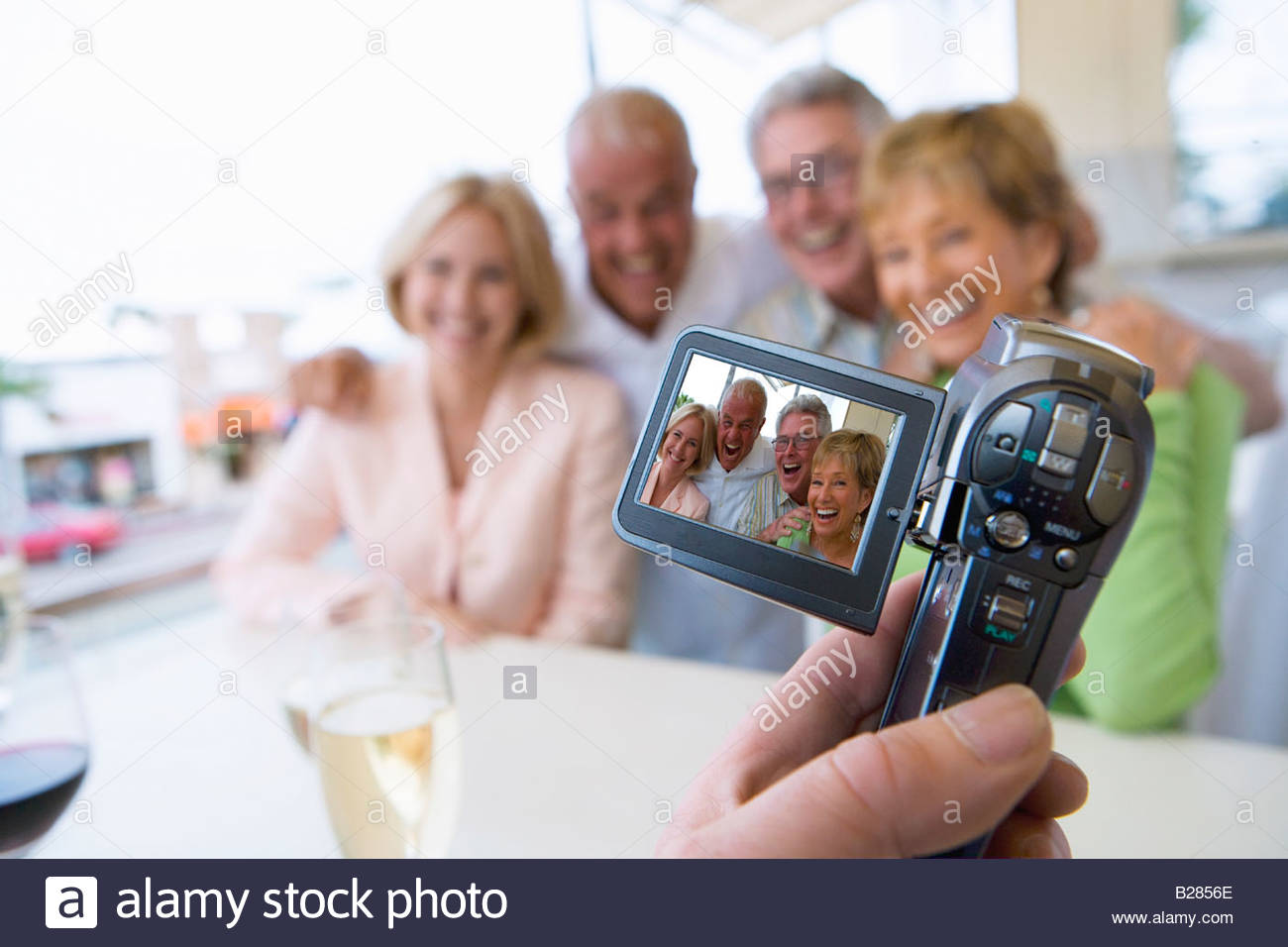 Man recording friends with video camera - Stock Image