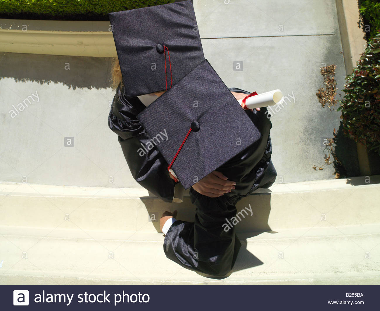 Graduates in caps and gowns in conversation, elevated view - Stock Image