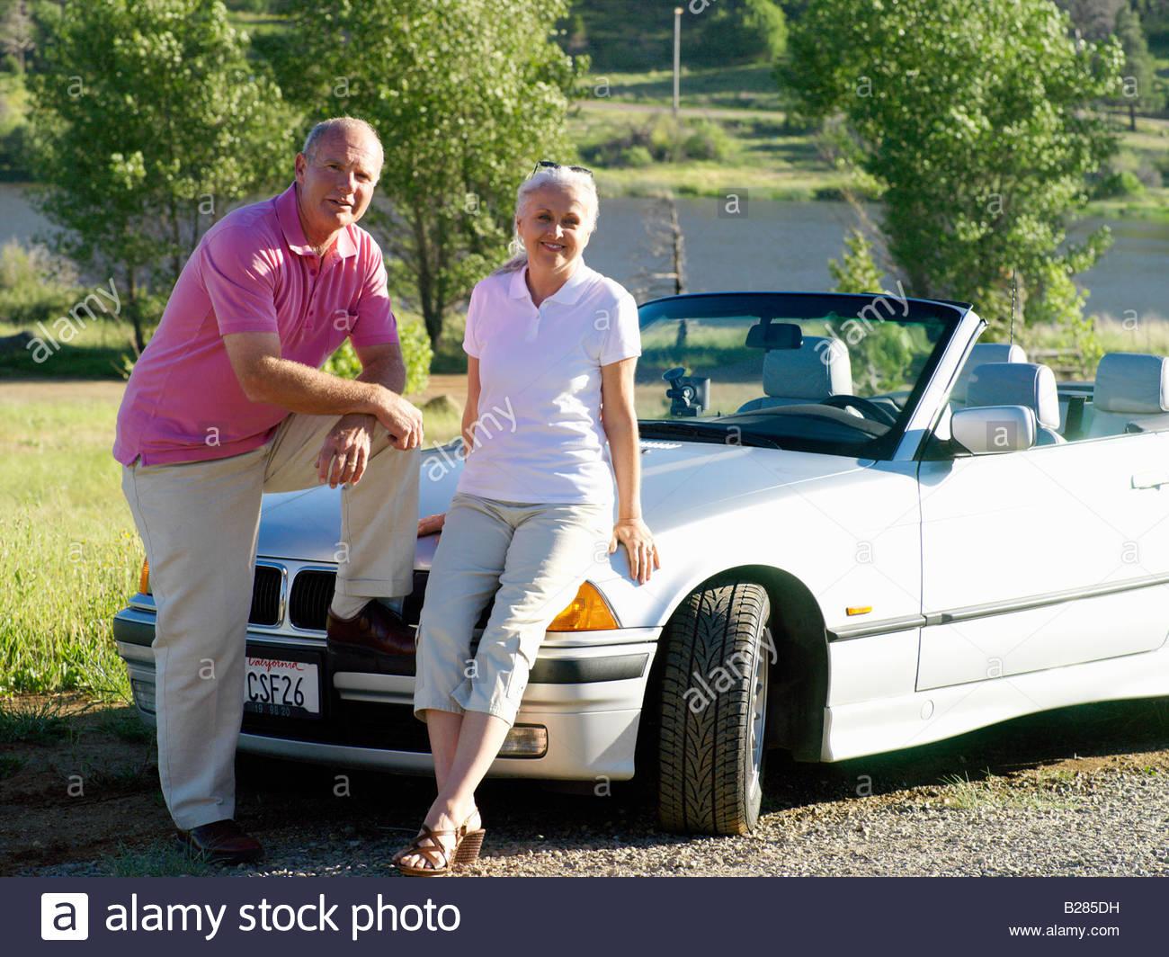 Couple on bonnet of convertible car, portrait - Stock Image