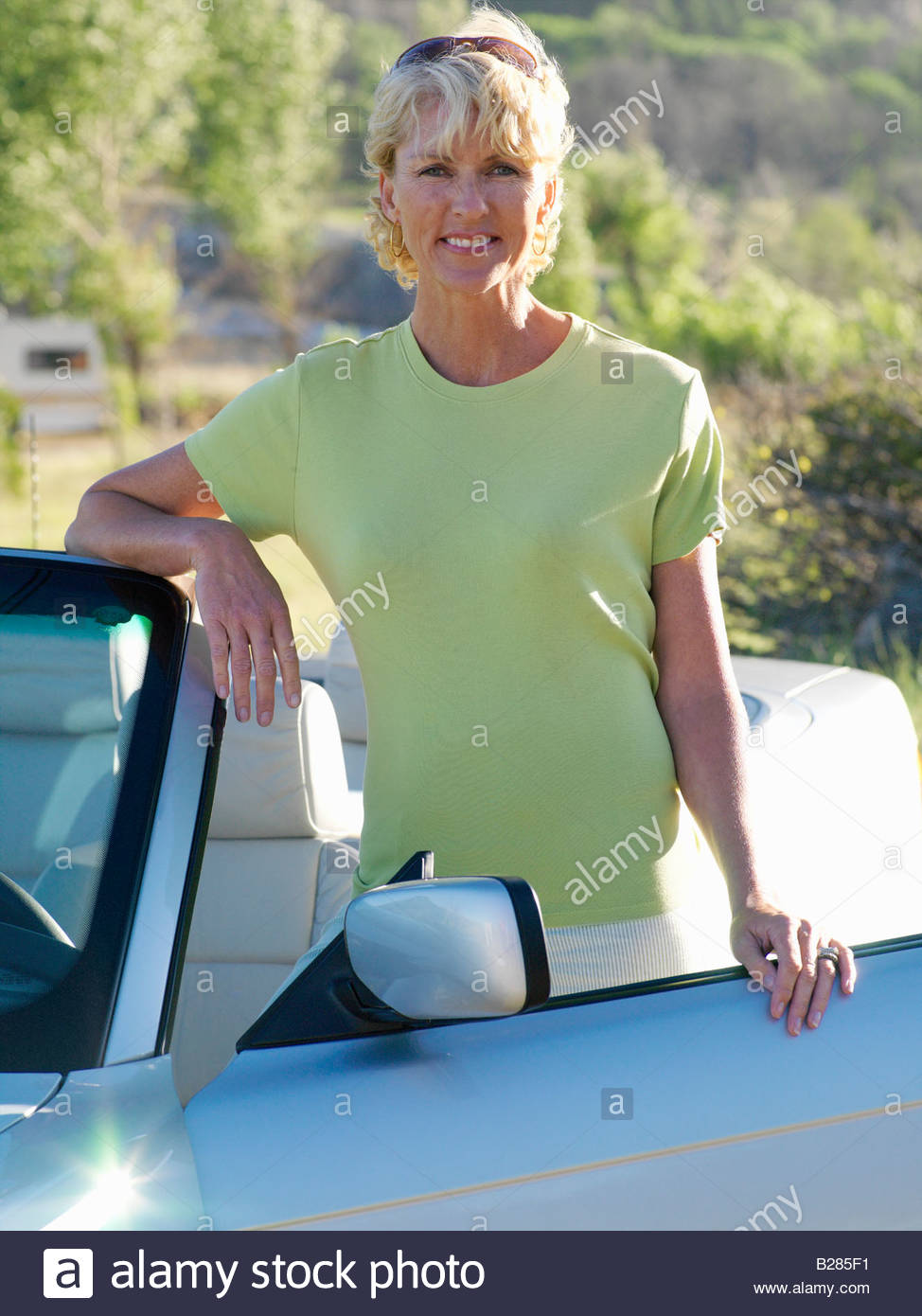 Mature woman by convertible car, smiling, portrait - Stock Image