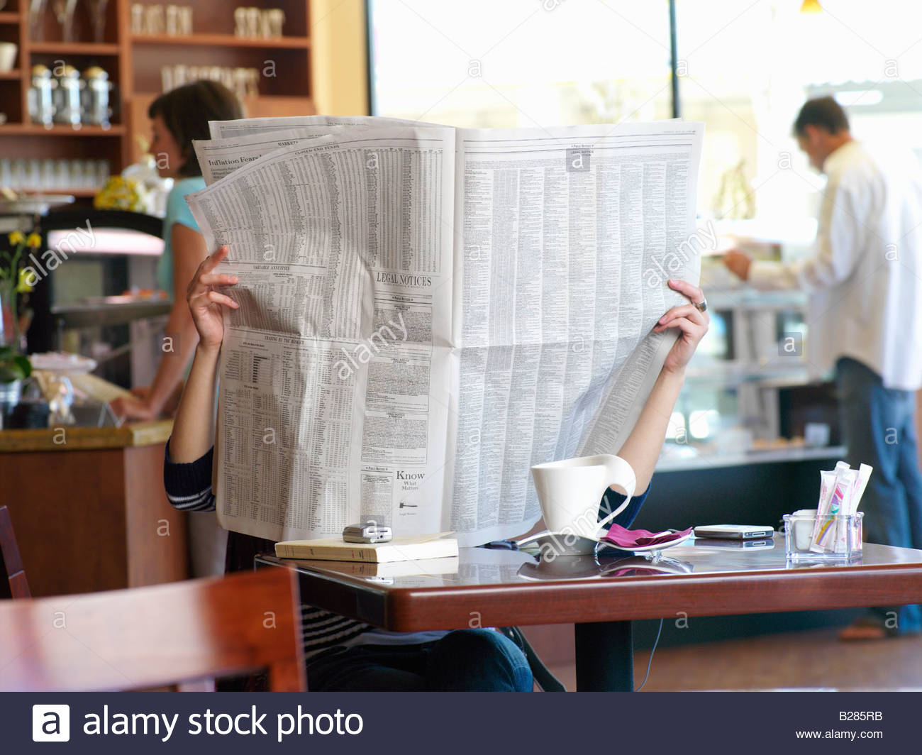 Woman with face obscured by newspaper in cafe - Stock Image