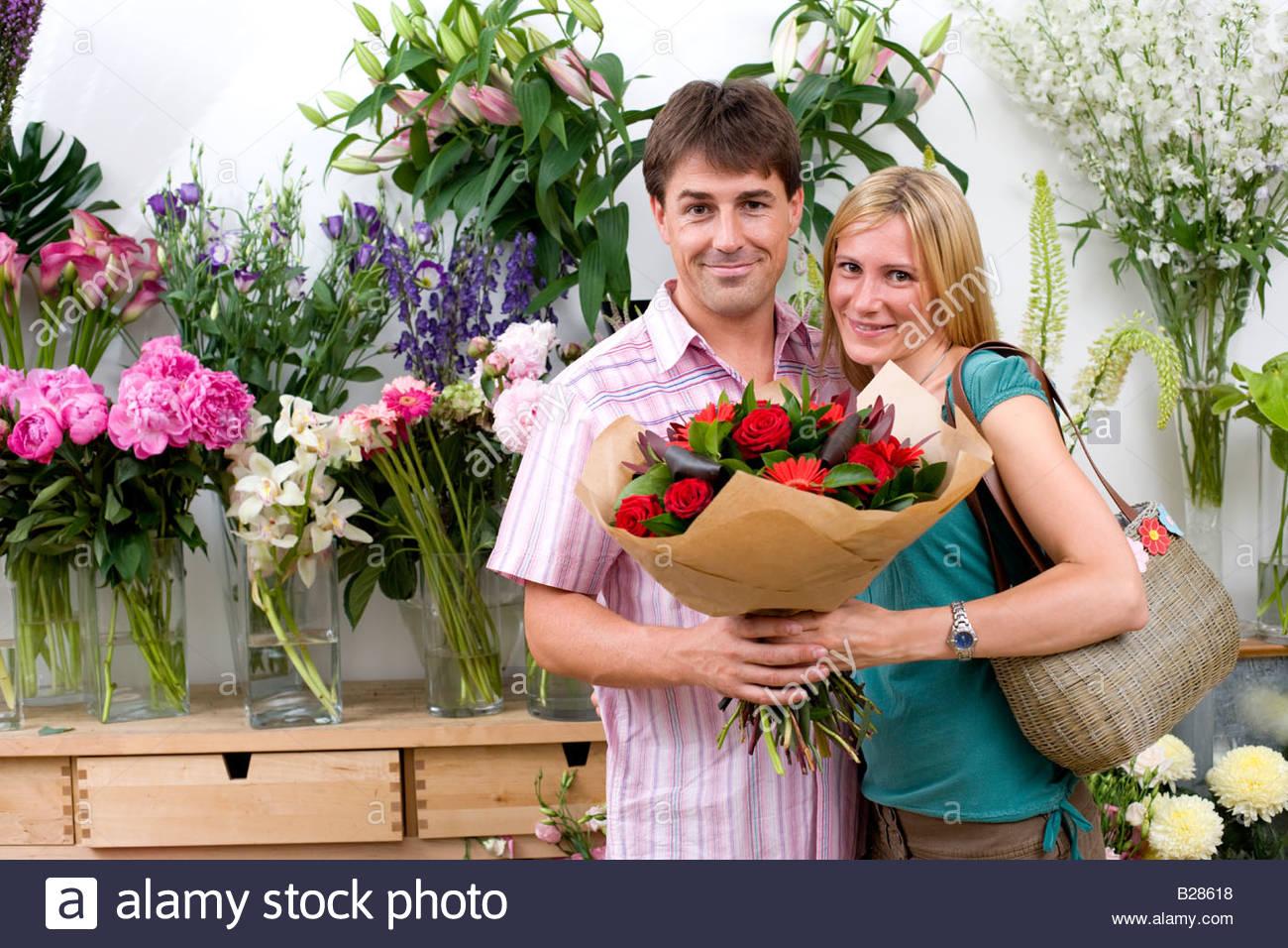 Bouquet flowers hands giving stock photos bouquet flowers hands couple with bouquet of flowers in shop smiling portrait stock image izmirmasajfo