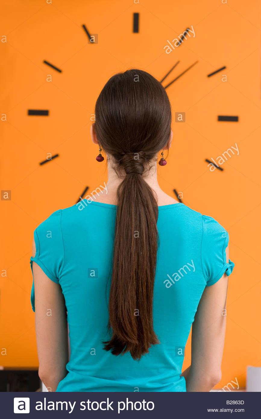 Woman looking at wall clock, rear view - Stock Image
