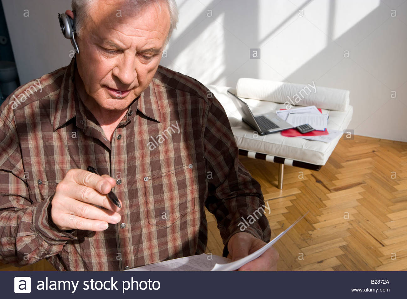 Senior man with paperwork and hands-free device - Stock Image