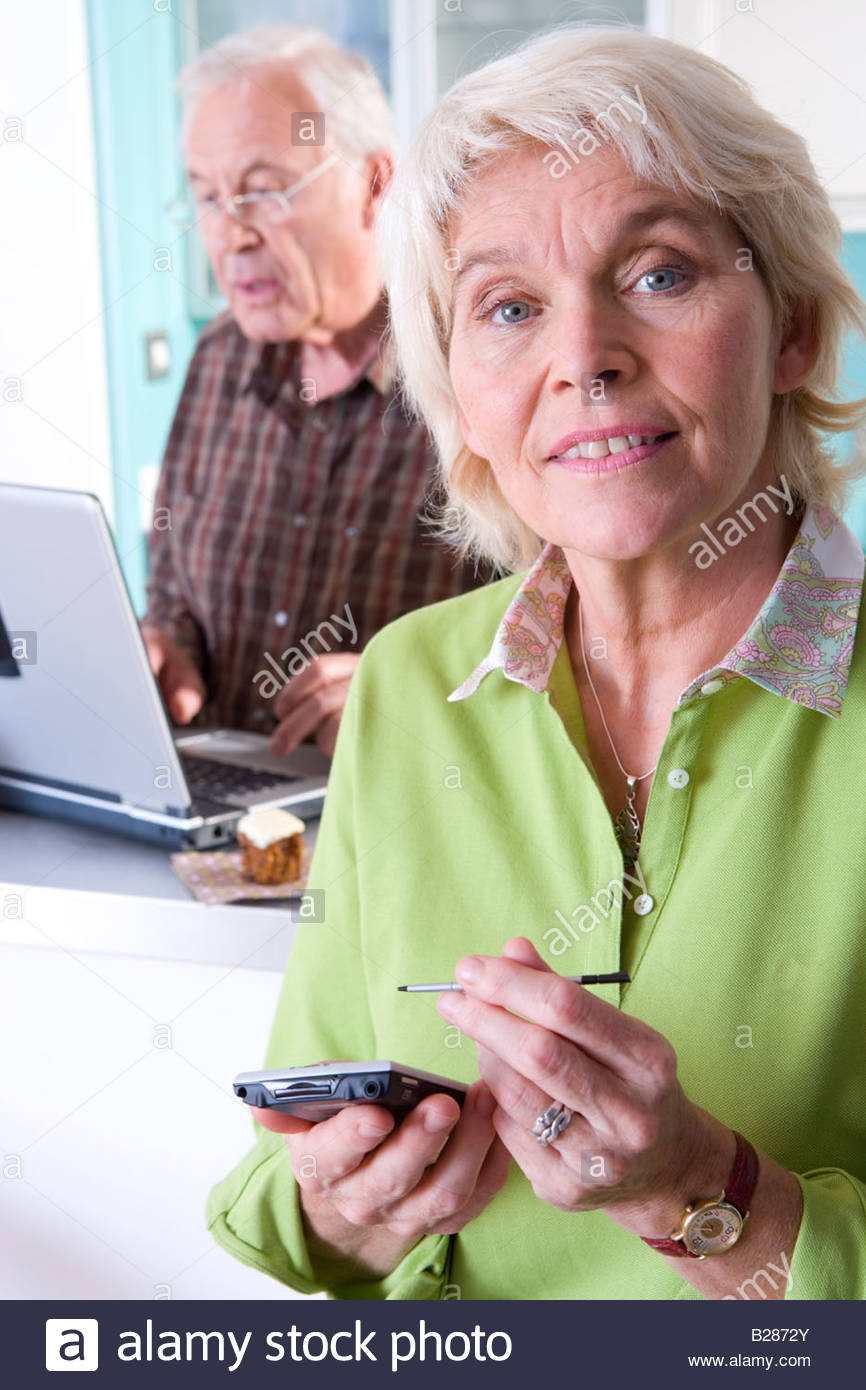 Senior couple with laptop computer and paperwork, portrait - Stock Image