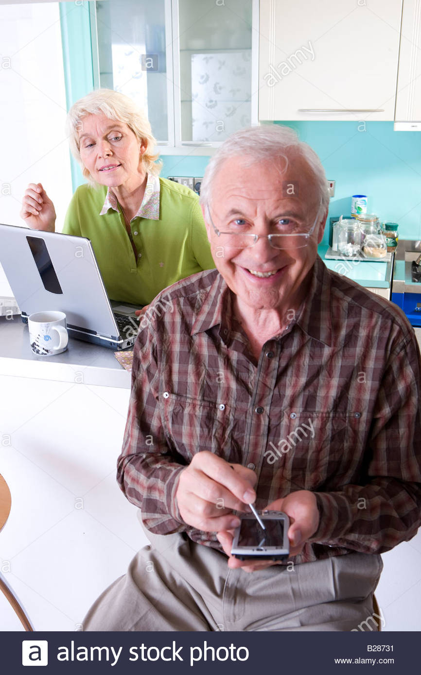 Senior couple with laptop computer and electronic organiser, portrait - Stock Image