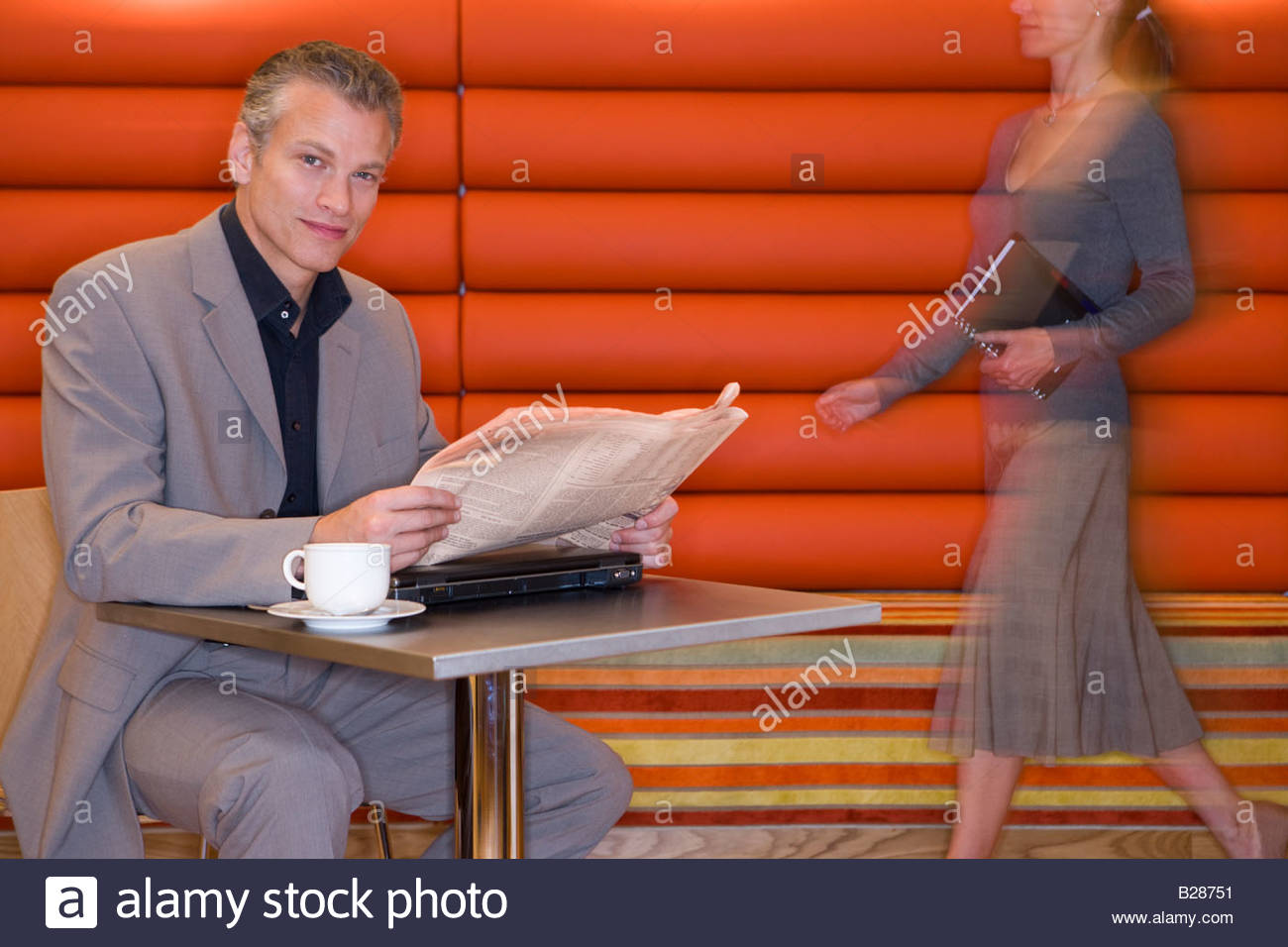 Businessman with laptop computer and newspaper in cafe, portrait - Stock Image