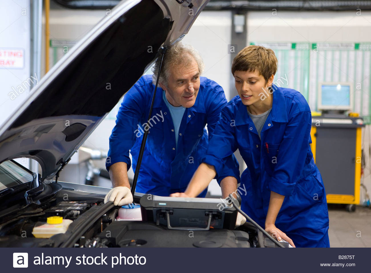 Mechanic and colleague with electronic diagnostics device - Stock Image