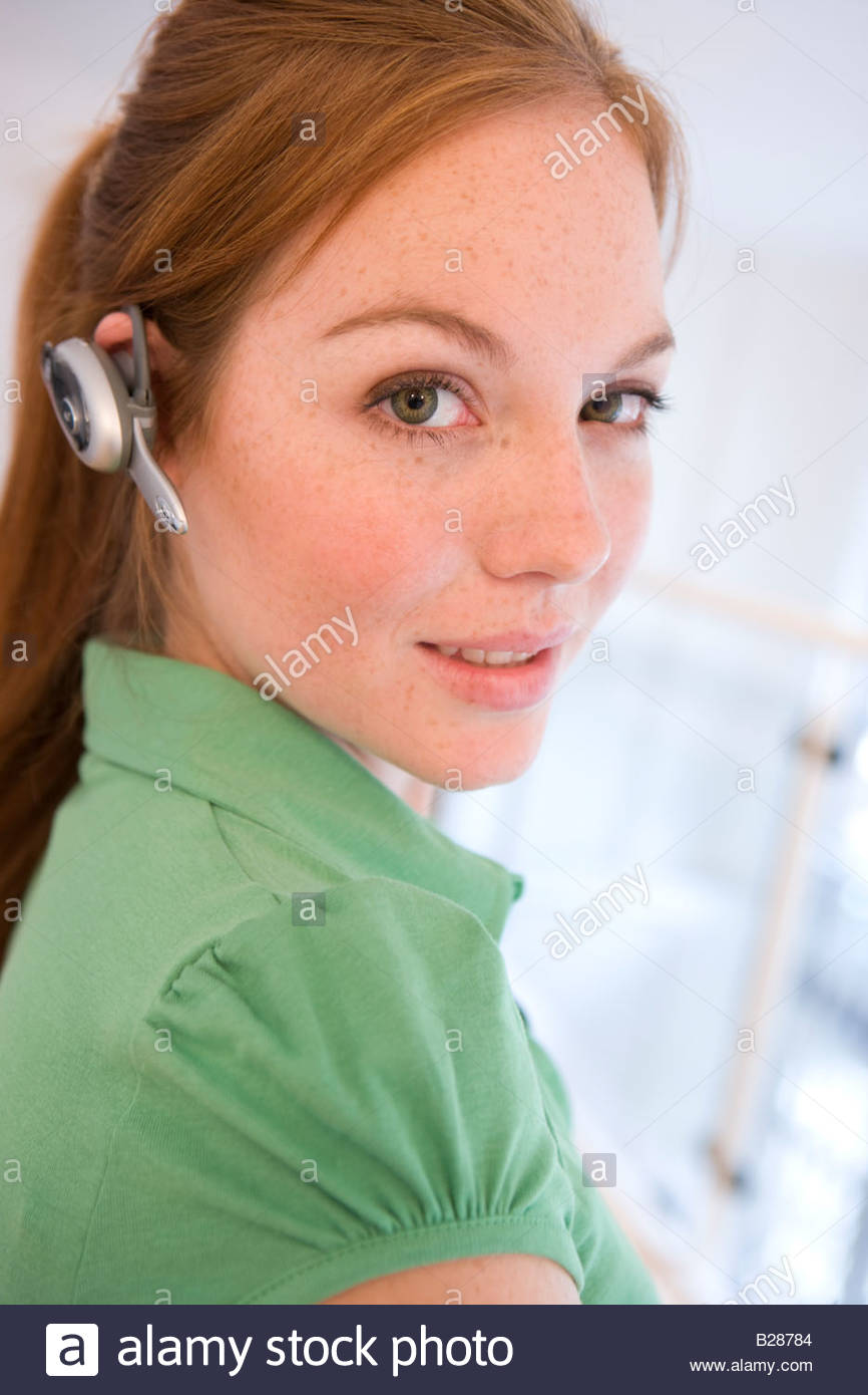 Woman with hands free device, portrait - Stock Image
